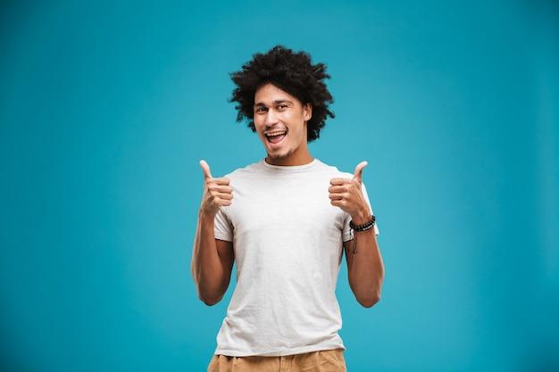 Enthousiaste jeune homme bouclé africain fait le geste de pouce en l'air.