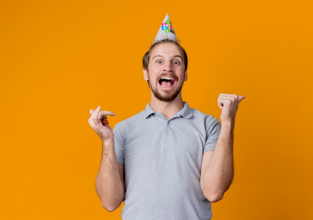 Enthousiaste jeune homme avec chapeau de vacances célébrant la fête d'anniversaire fou heureux et excité debout sur le mur orange