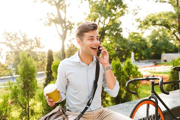 Enthousiaste jeune homme élégant parlant au téléphone mobile
