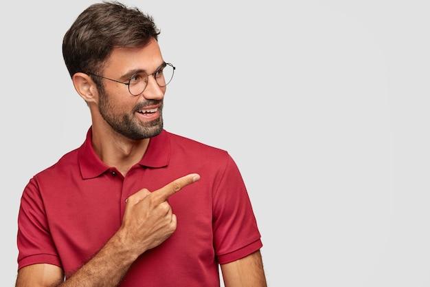 Enthousiaste jeune homme émotionnel posant contre le mur blanc