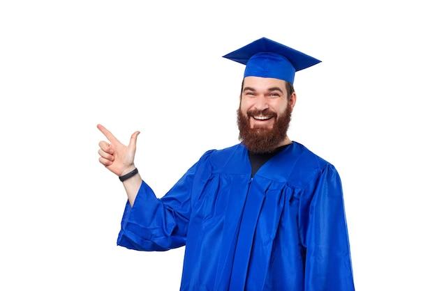 Enthousiaste jeune homme étudiant barbu portant baccalauréat et bonnet de graduation et pointant vers l'extérieur