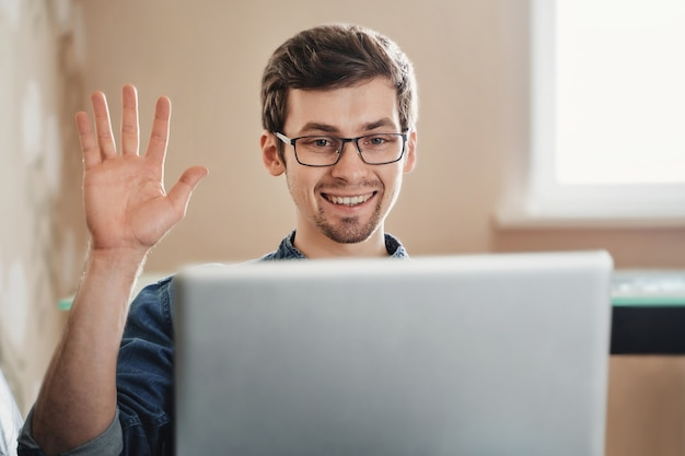 Enthousiaste jeune homme européen faisant un geste `` bonjour '' à la caméra web lors d'une conférence en ligne à la maison