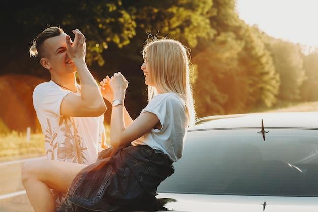 Enthousiaste jeune homme et femme riant de voiture garée au bord de la route dans la nature