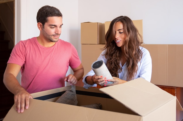 Enthousiaste jeune homme et femme se déplaçant et déballant des choses, ouvrant une boîte en carton et sortant de l'objet