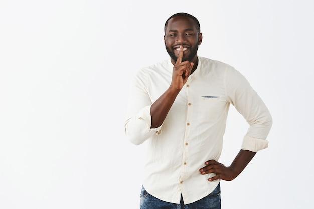 Enthousiaste jeune homme heureux posant contre le mur blanc