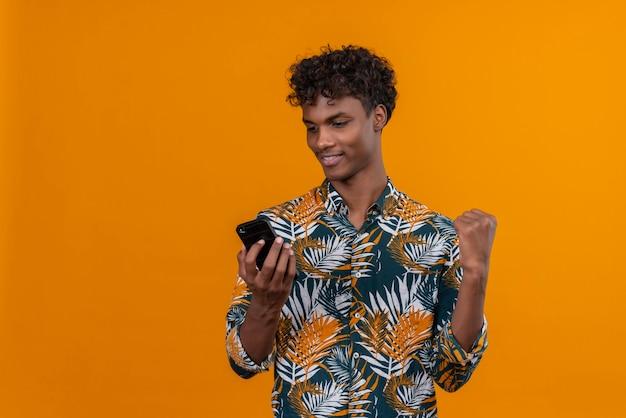 Enthousiaste jeune homme à la peau foncée et aux cheveux bouclés en chemise imprimée de feuilles à la recherche de smartphone avec le poing serré