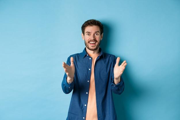 Enthousiaste jeune homme pointant les mains vers la caméra et souriant, se sentant heureux pour vous, louant le bon travail, debout sur fond bleu.