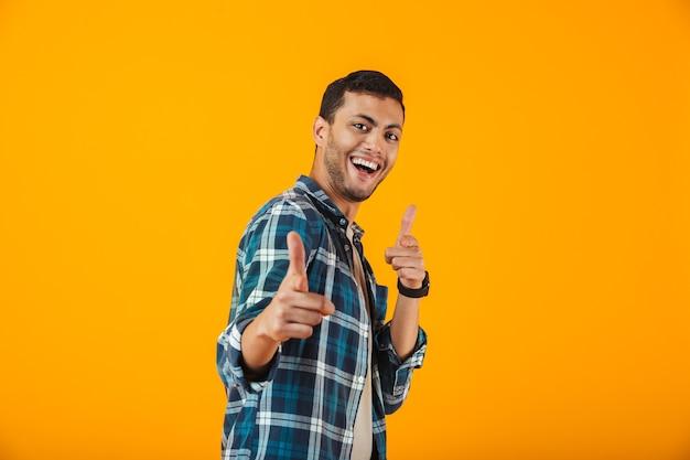 Enthousiaste jeune homme portant une chemise à carreaux debout isolé sur un mur orange, pointant la caméra