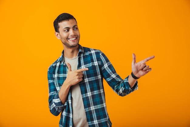 Enthousiaste jeune homme portant une chemise à carreaux debout isolé sur un mur orange, pointant le doigt sur l'espace de copie