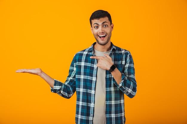 Enthousiaste jeune homme portant une chemise à carreaux debout isolé sur un mur orange, présentant un espace de copie sur sa paume