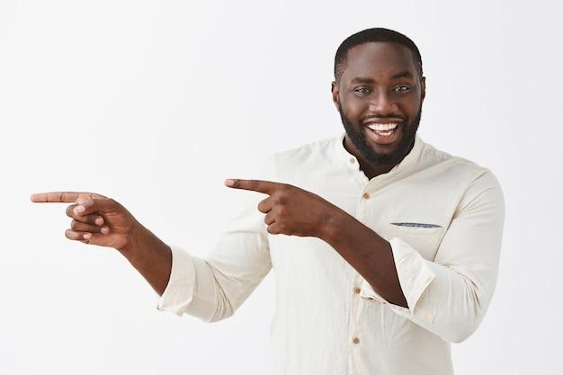 Enthousiaste jeune homme posant contre le mur blanc