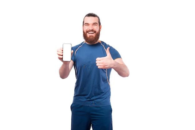 Enthousiaste jeune homme de remise en forme montrant un écran blanc sur smartphone et pouce vers le haut