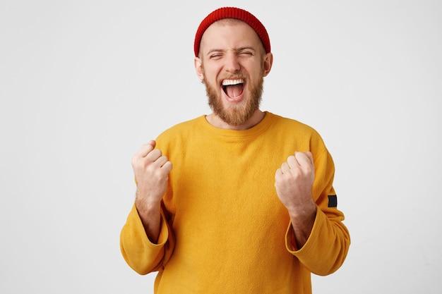 Enthousiaste jeune homme séduisant célébrant son succès