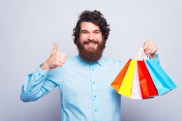 Enthousiaste jeune homme souriant à la caméra et tenant des sacs à provisions et un pouce vers le haut