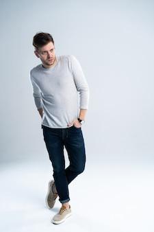 Enthousiaste jeune homme tenant les mains dans les poches et regardant la caméra en se tenant debout sur fond blanc