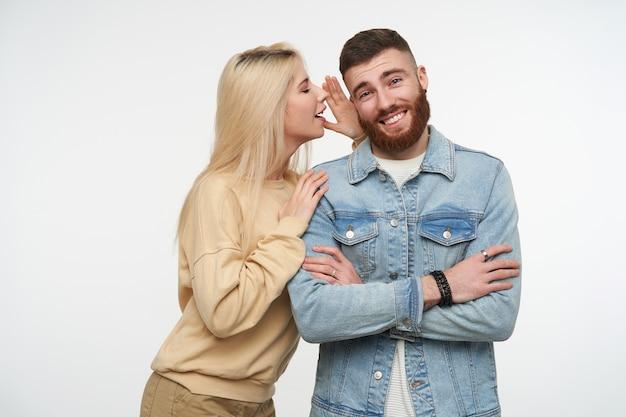 Enthousiaste jeune mec charmant brune barbu croisant les mains sur sa poitrine tout en écoutant sa jolie petite amie blonde aux cheveux longs, isolée sur blanc