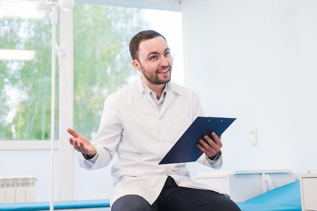Enthousiaste jeune médecin tenant un presse-papiers et faisant des gestes avec la main à l'hôpital