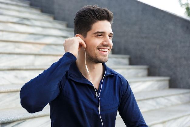 Enthousiaste jeune sportif écoutant de la musique avec des écouteurs alors qu'il était assis à l'extérieur