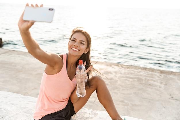 Enthousiaste jeune sportive au repos après l'entraînement à la plage, prenant un selfie, eau potable