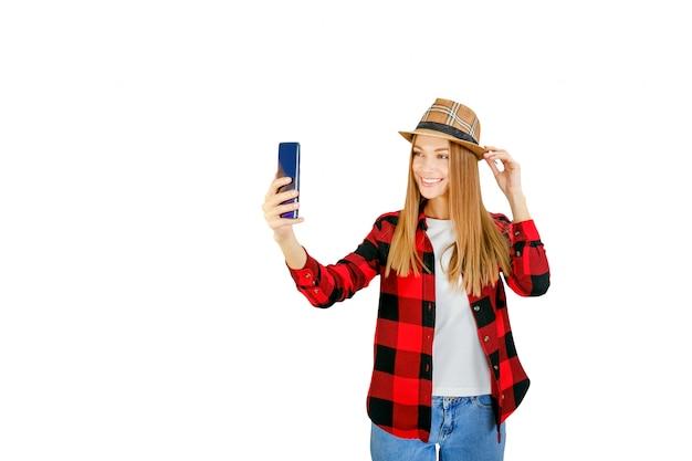 Enthousiaste jeune womanblooger prendre selfie isolé sur blanc. élégante jeune femme avec téléphone souriant.
