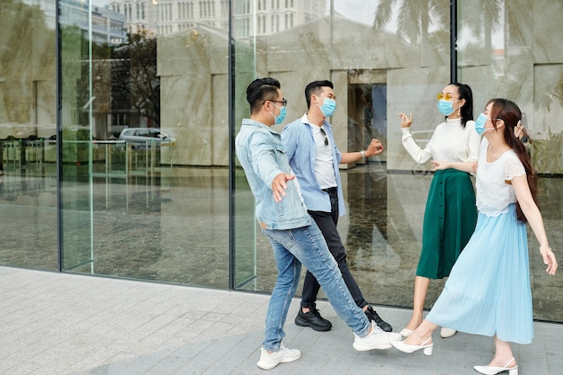 Enthousiaste jeunes asiatiques dans des masques de protection touchant les orteils les uns des autres au lieu de cinq ou poignée de main