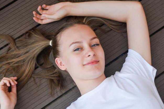 Enthousiaste joli gosse, adolescente, être de bonne humeur et lui montrer son sourire et ses cheveux longs.