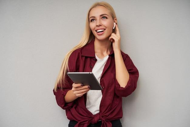 Enthousiaste jolie femme blonde aux cheveux longs regardant joyeusement vers le haut et tenant l'index sur l'écouteur dans son oreille, étant de bonne humeur en se tenant debout sur un fond gris clair