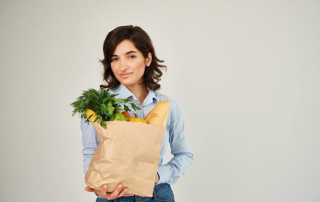 Enthousiaste jolie femme dans une chemise avec un paquet de produits de livraison d'aliments sains ménagers