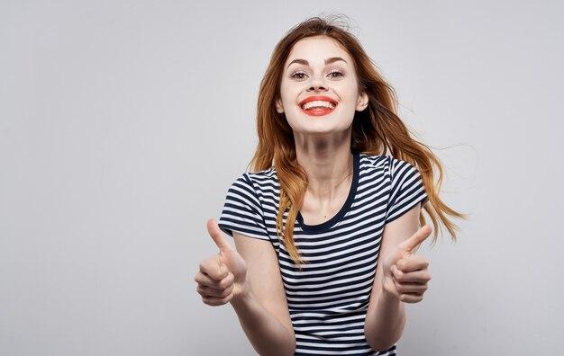 Enthousiaste jolie femme rayé t-shirts lèvres rouges émotions studio. photo de haute qualité
