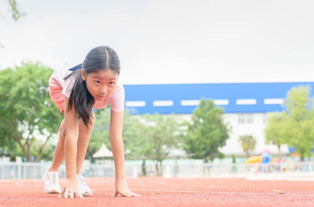 Enthousiaste jolie fille en position prête à courir sur piste,