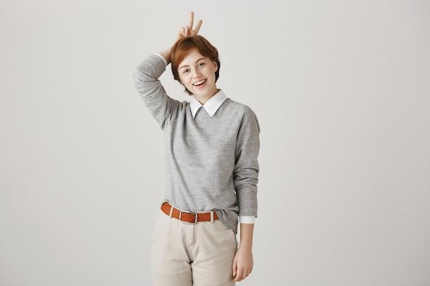 Enthousiaste jolie fille rousse avec coupe courte posant contre le mur blanc
