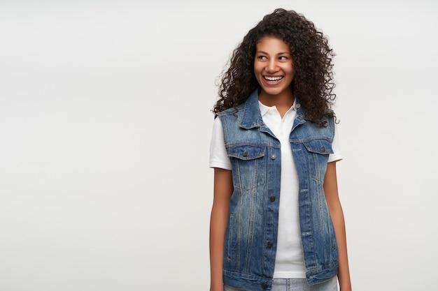 Enthousiaste jolie jeune femme brune bouclée avec une peau foncée debout sur blanc avec les mains vers le bas, regardant de côté joyeusement avec un sourire charmant, étant en pleine forme