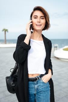 Enthousiaste jolie jeune femme marchant et parlant au téléphone portable à l'extérieur