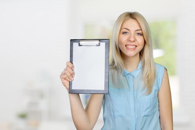 Enthousiaste jolie jeune femme montrant le presse-papiers vide