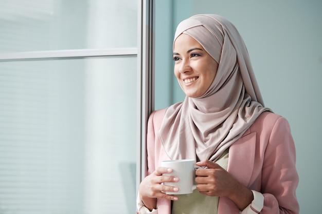 Enthousiaste jolie jeune femme musulmane en hijab rose debout à la porte et tenant la tasse tout en regardant ailleurs
