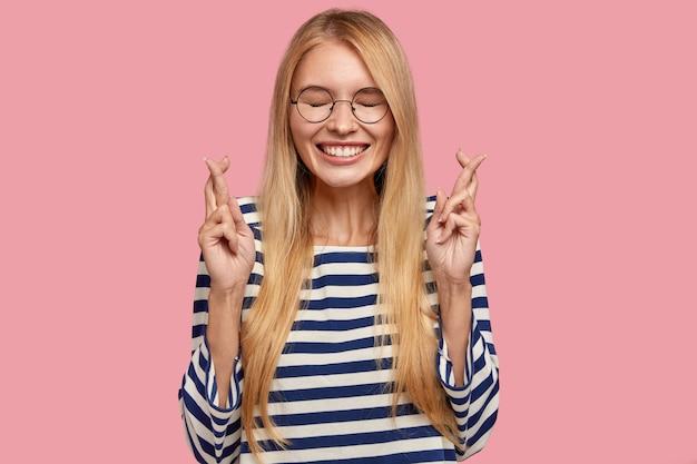 Enthousiaste jolie jeune femme avec un sourire à pleines dents, croise les doigts comme le souhaite