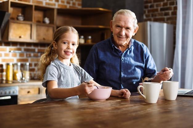 Enthousiaste jolie petite fille mangeant des céréales tout en profitant de son petit-déjeuner avec grand-père