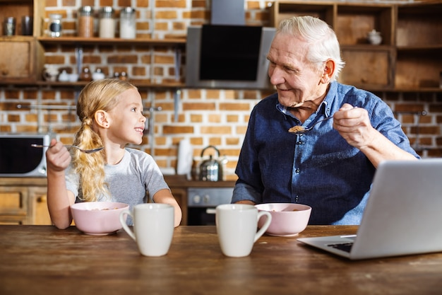 Enthousiaste mignonne petite fille mangeant des céréales tout en appréciant le petit déjeuner tôt avec son gradfather