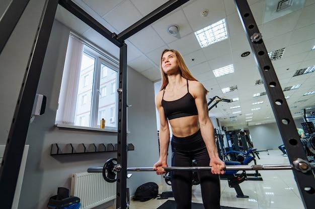 Enthousiaste musculaire jeune femme portant une combinaison noire prenant haltère pour faire des exercices de levage en salle de sport