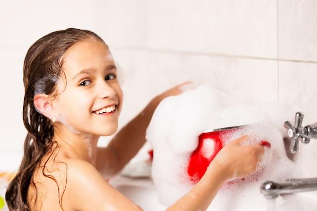 Enthousiaste petite fille caucasienne joue avec de la mousse tout en se baignant dans la baignoire pendant la quarantaine