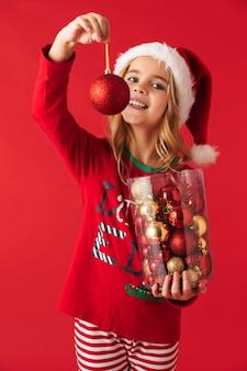 Enthousiaste petite fille portant le costume de noël debout isolé, tenant un ensemble de jouets d'arbre de noël
