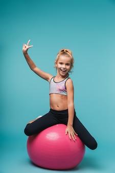 Enthousiaste petite fille portant des vêtements de sport, faire des exercices avec ballon de fitness isolé sur mur bleu