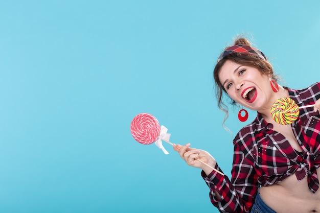 Enthousiaste rire jolie jeune femme dans des vêtements rétro posant sur une surface bleue avec une sucette montrant le côté droit