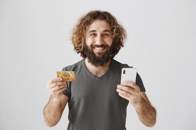 Enthousiaste souriant homme barbu du moyen-orient commande en ligne, shopping avec carte de crédit et smartphone