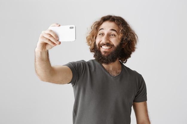 Enthousiaste souriant homme du moyen-orient prenant selfie avec smartphone