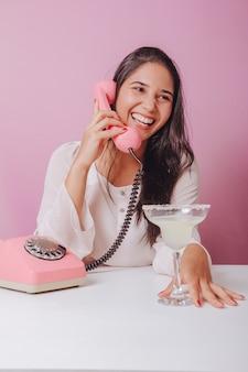 Enthousiaste et souriante jeune femme brune avec boisson, utilise un téléphone vintage. portrait sur une surface rose