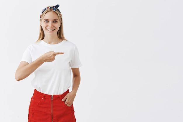 Enthousiaste souriante jeune fille blonde posant contre le mur blanc