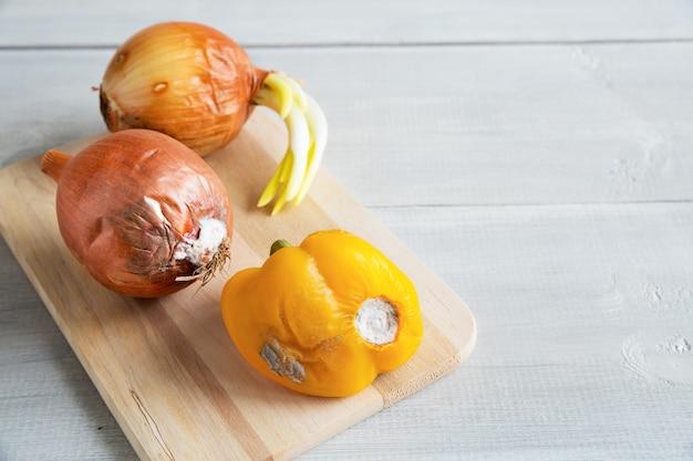 Entier pourri gâté avec des légumes de moisissure sur planche de bois sur fond blanc avec copie espace