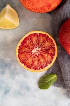 Entiers et coupés en demi-sang oranges siciliennes, citrons verts et menthe sur une surface en béton bleu