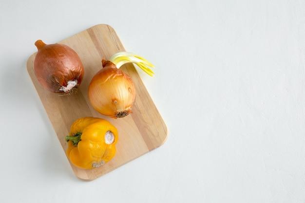 Entiers gâtés, oignons et poivrons pourris sur planche de bois à plat sur fond blanc avec place pour le texte.